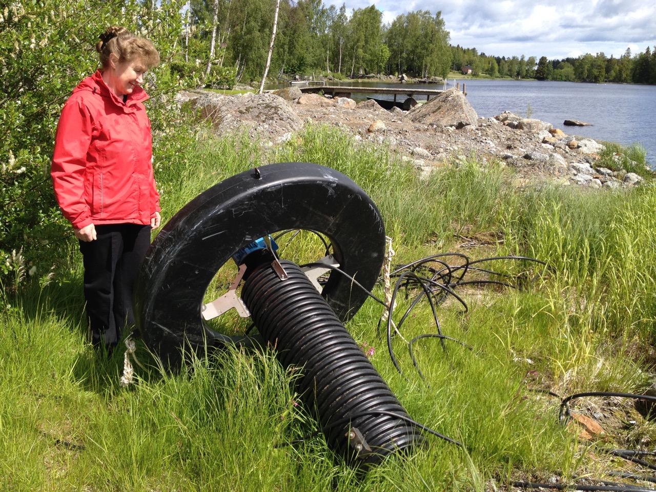 Ulla-Maarit Raitanen granskar en av syrepumparna som för sommaren är upptagna på stranden.