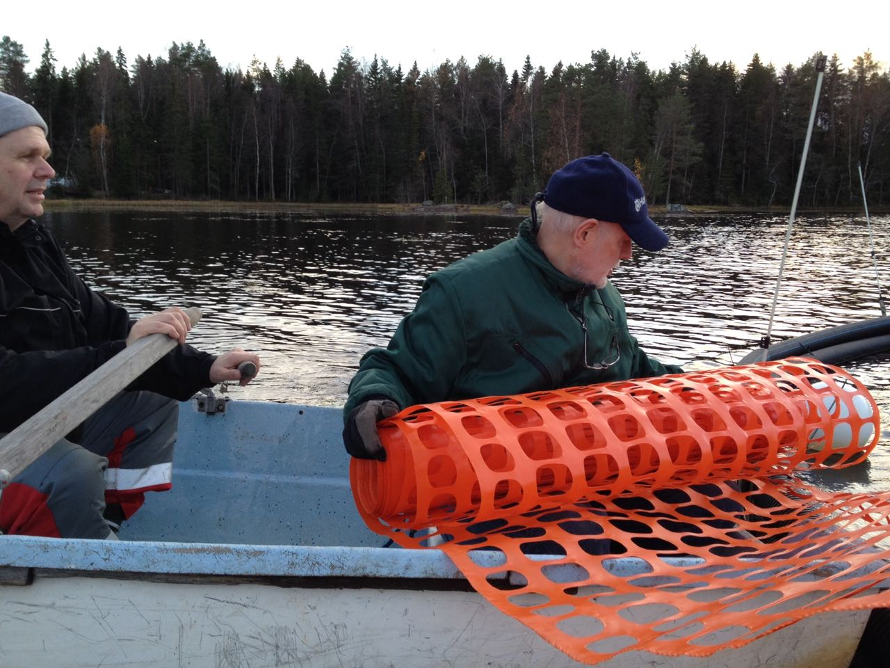 Jukka rullar ut plastnätet medan Bengt sköter årorna.