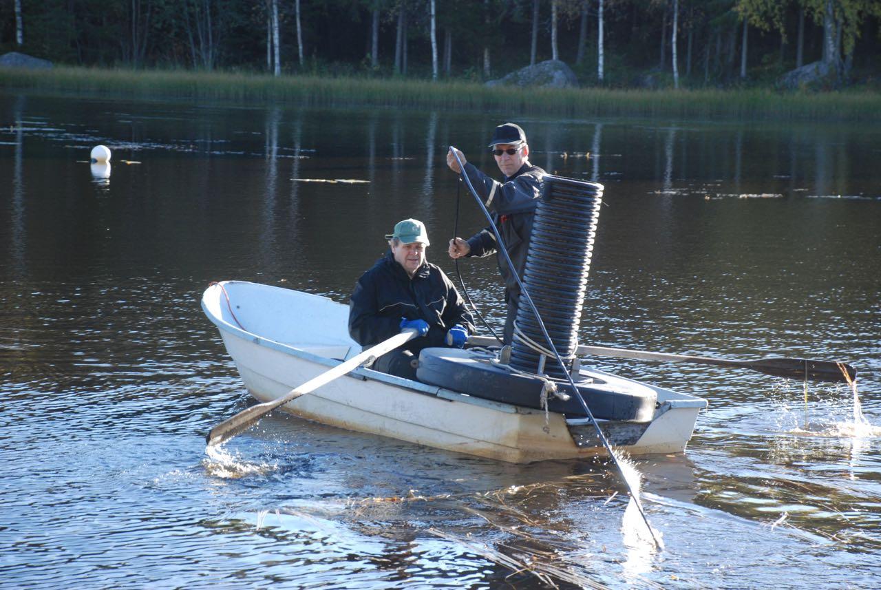 """Och här är en av syrepumparna på väg ut på sjön. Bengt ror och Rune """"fiskar"""", dvs. kollar att elkabeln kommer rätt."""