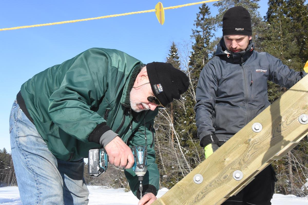 Byggmästaren Jukka skruvar medan konstruktören Markos övervakar.