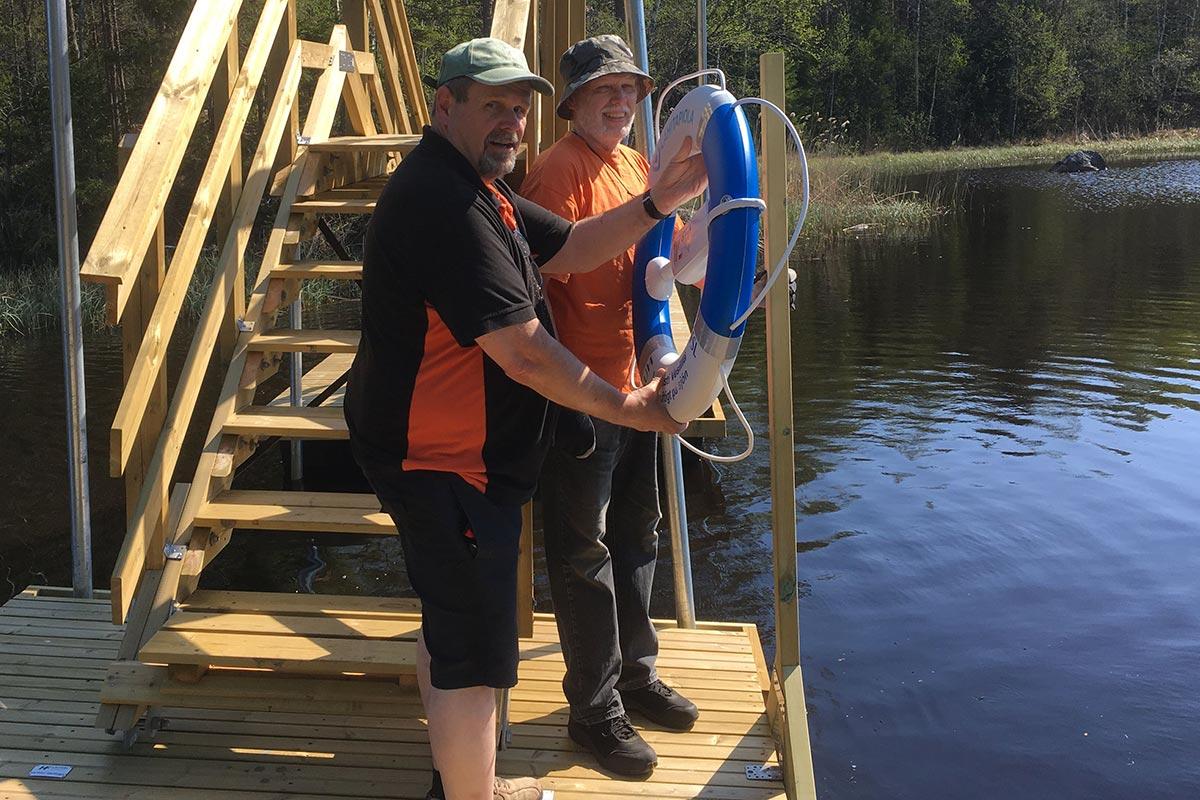 En livboj har donerats av Lokaltapiola. Säkerheten är viktig! Jukka har fixat en ställning som han fäster bojen på tillsammans med Bengt.