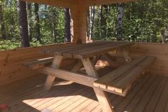 Bord och bänkar är monterade i paviljongen.